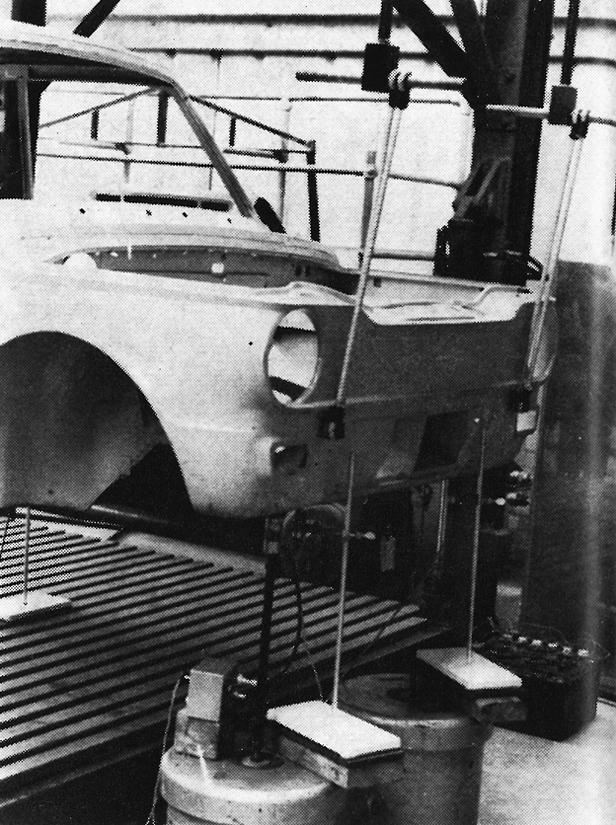 Zwei elektrische Vibratoren durchrütteln gerade die Karosserie eines Hillman-Imp, die in einem Testrahmen zu Studienzwecken befestigt ist.