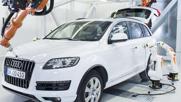 An einem Auto von Audi wird mittels Roboterarmen gerabeitet