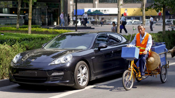 Der Porsche Panamera in China, daneben ein Chinese am Fahrrad