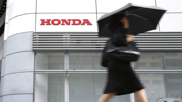 Frau mit Regenschrim geht an einem Honda-Schild vorbei