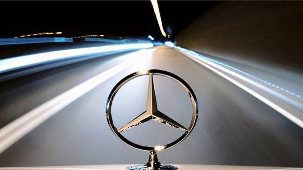 Ein Mercedes-Auto fährt durch einen Tunnel. Man sieht nur den Mercedes-Stern scharf.