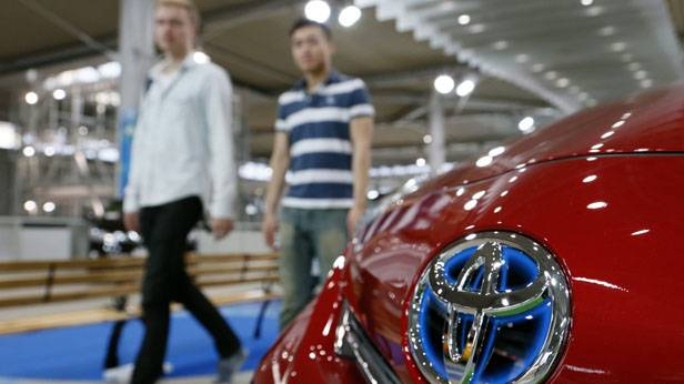 Zwei Besucher einer Automesse schauen auf ein Auto von Toyota