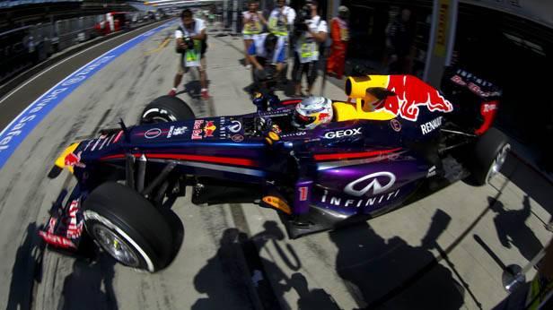Sebastian Vettel in seinem Rennauto umzingelt von Fotografen.