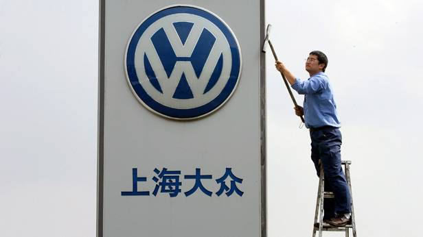 Mitarbeiter reinigt das VW-Firmenschild (China)