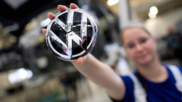Eine Werksarbeiterin von VW hält ein VW-Logo in die Höhe
