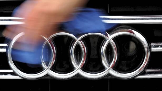 Eine Hand wischt mit einem Tuch über den Kühlergrill eines Audis.
