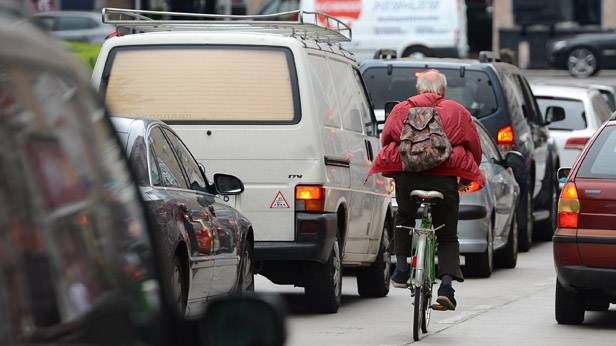Ein Fahrradfahrer im dichten Verkehr.