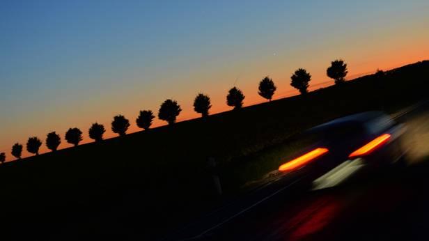 Ein Auto auf einer Landstrasse im Sonnenuntergang