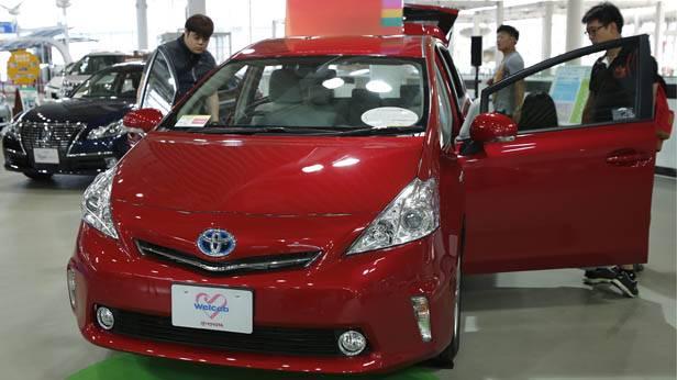 Besucher schauen sich auf einer Automesse den Toyota Prius Alpha Hybrid an.