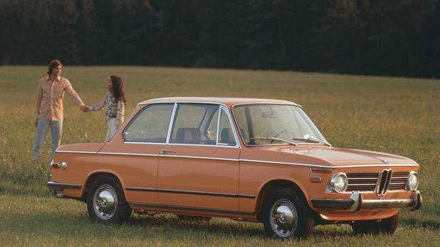 Der BMW 2002 steht in einem Feld, ein Paar daneben, hält Hände