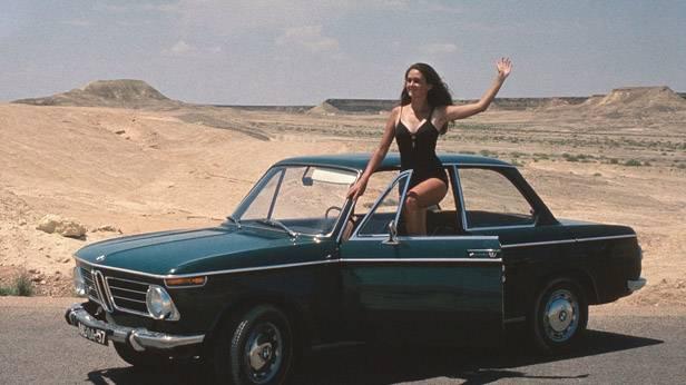 Eine Frau im Badeanzug winkt aus einem BMW