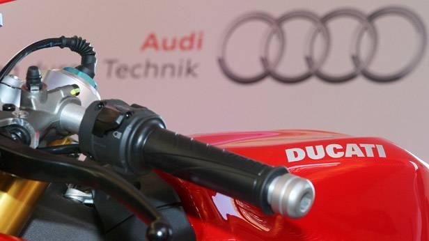Ein Motorrad von Ducati, dahinter das Logo von Audi