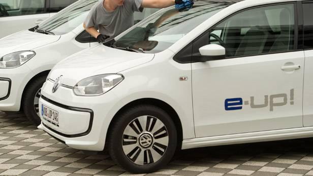 Ein Arbeiter putzt die Scheibe eines VW E-Ups