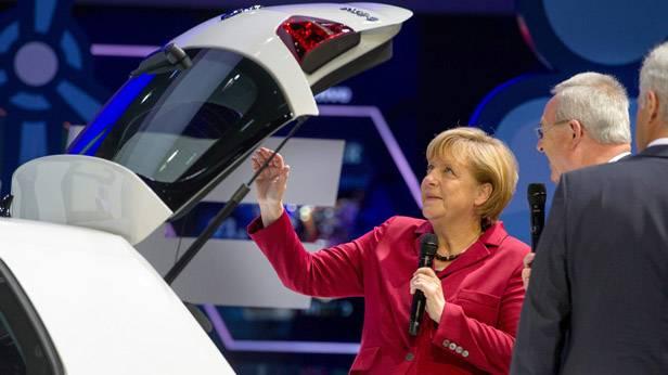Angela Merkel steht beim offenen Kofferraum des e-Golf auf der IAA in Frankfurt