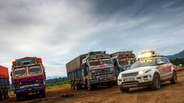 Ein Land Rover vor vier Lastwagen in Nepal