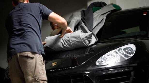 Die Plane, unter der der Porsche Macan ist, wird enthüllt