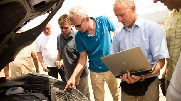 4 Männer schauen in den Motorram des Porsche Macan