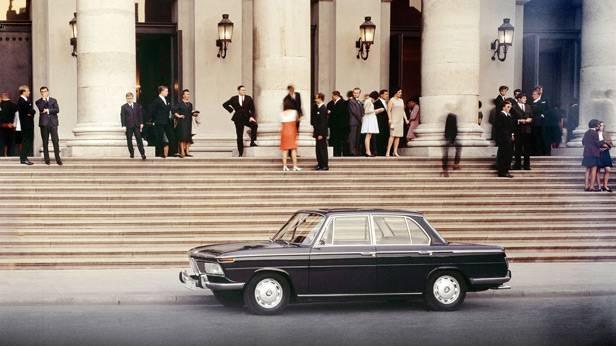 Der BMW 1800 seitlich, vor einem großen Gebäude