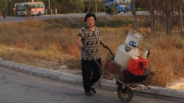 Eine Frau in China mit einem Milchwagen