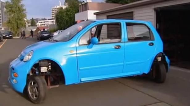 Ein blaues Auto parkt richtig quer ein.