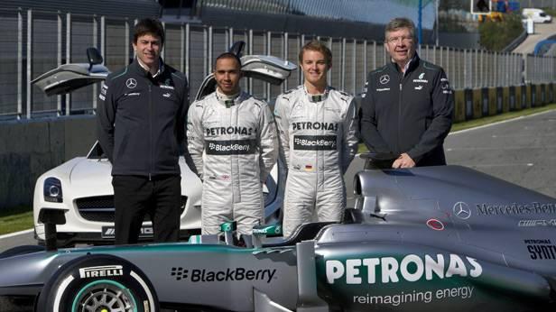 Gruppenfoto von Mercedes Wolf, Hamilton, Rosber, Brawn stehn hinter dem Rennauto
