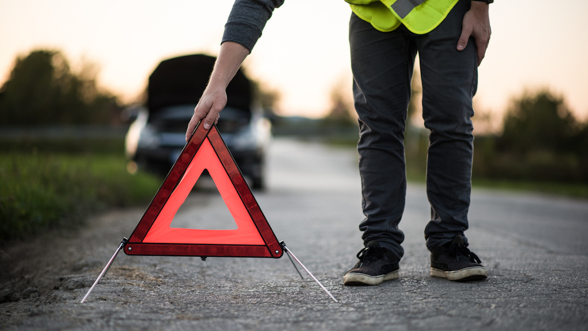 Autofahrer stellt das Pannendreieck am Straßenrand auf.