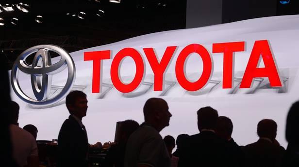 Das Logo von Toyota, davor Menschen