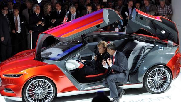 Angela Merkel und Bernhard Mattes sitzen in einem Ford Evos auf der IAA 2011