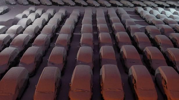 Eingeschneite Neuwagen von Opel auf einem Parkplatz