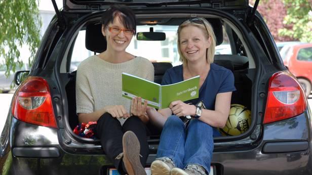 Zwei Frauen sitzen in einem Kofferraum.