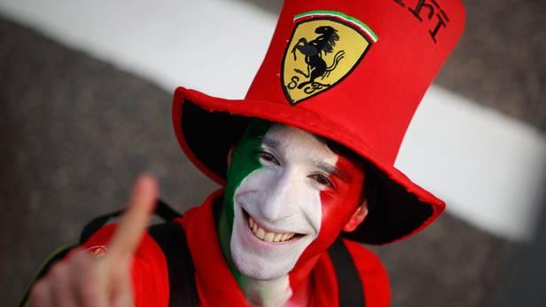 Ein Fan von Ferrari mit angemaltem Gesicht und Ferrari-Hut