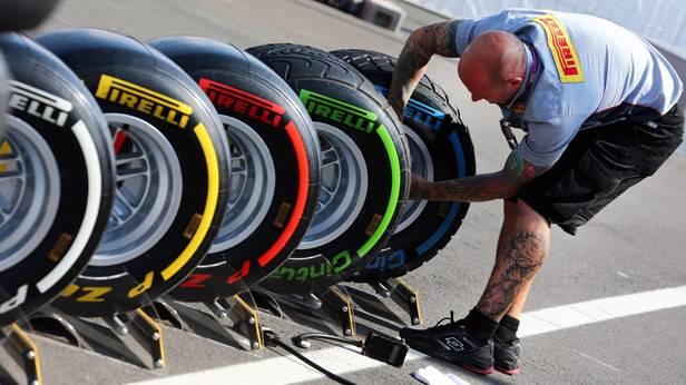 Ein Mechaniker von Pirelli richtet Reifen ein.