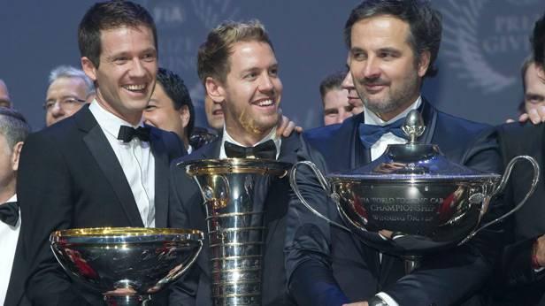 Sebastien Ogier, Sebastian Vettel und Yvan Muller mit ihren WM-Trophäen