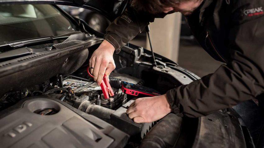 Anschließen eines Starterkabels im Motorraum eines Autos um Starthilfe geben zu können.