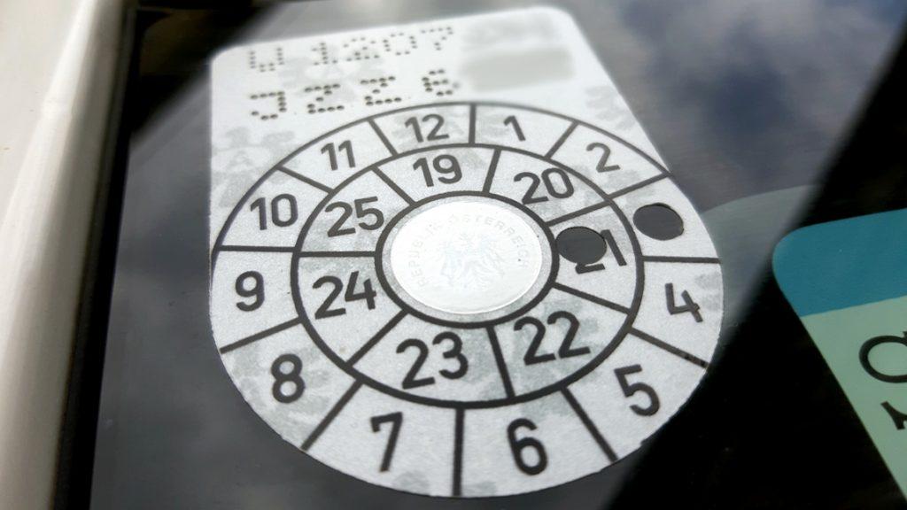 Ein Pickerl (57a-Überprüfung) auf der Windschutzscheibe eines Autos.