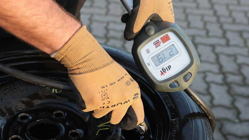 Der Reifendruck wird mit einem Messgerät kontrolliert.