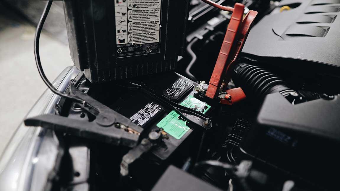Der Motorraum eines Autos mit angeschlossenen Starterkabeln.